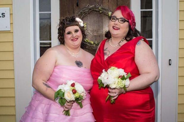 Δύο γυναίκες χαμογελούν προς την κάμερα κρατώντας λουλούδια τη μέρα του γάμου τους