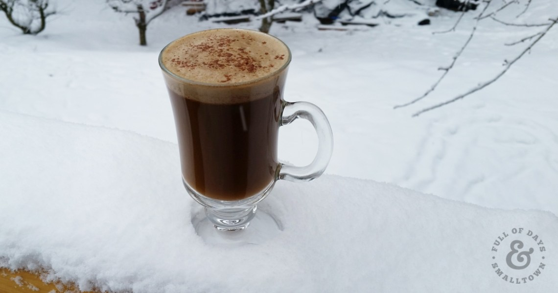 Gingerbread Latte sitting on a railing covered with snow