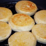 Sourdough English Muffins cooking in a cast iron pan