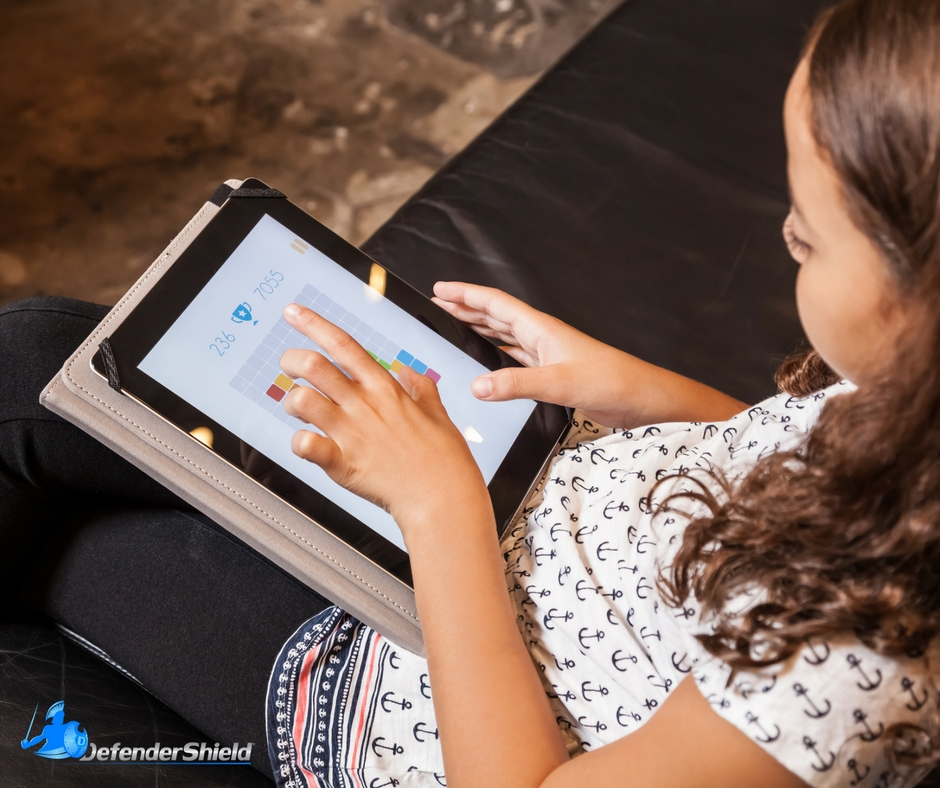 Little girl sitting on a couch with an iPad in a DefenderShield iPad Case