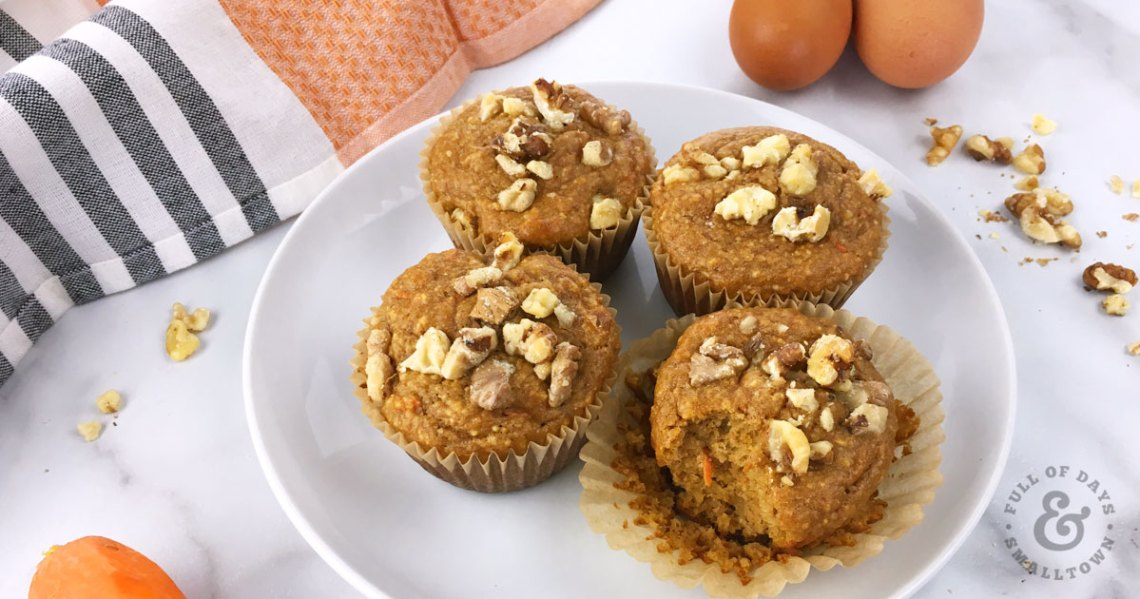 Gluten Free Paleo Carrot Cake Protein Muffins on a plate with eggs, walnuts and carrots in the background.