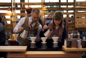 Two people pouring coffee in unison.