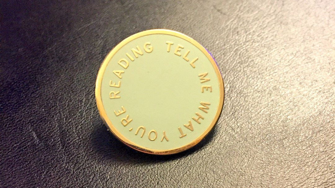 "Circular badge, with the words ""Tell Me What You Are Reading"""