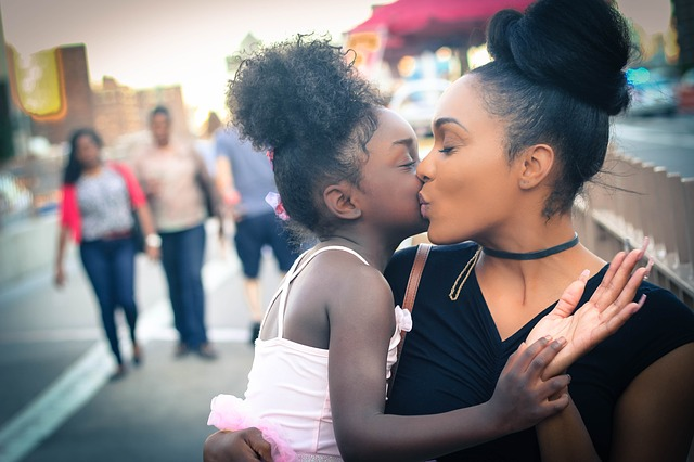 Mom kissing young daughter. Stuff parents say