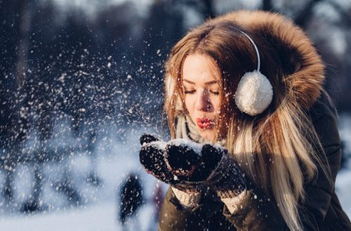 Girl blowing snow off her hands gently