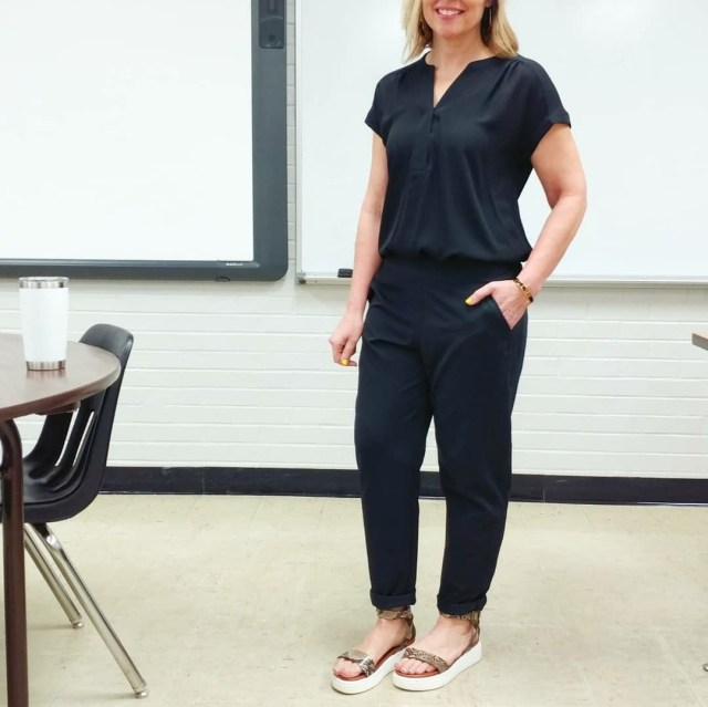 Teacher Outfit featuring faux jumpsuit that is actually a black top and joggers with snake print sporty sandals
