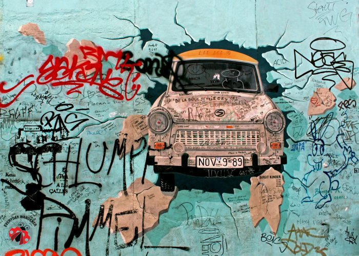 A Trabi bursts through the Berlin Wall at the East Side Gallery