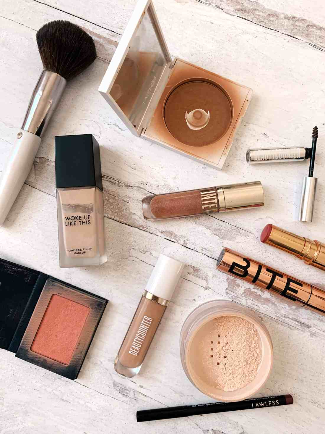 A variety of makeup products laying on a white wooden background.