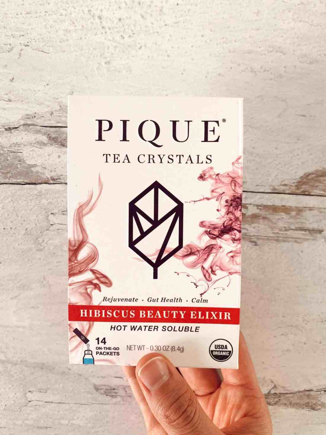 Holding the Pique Tea Hibiscus Beauty Elixir box.