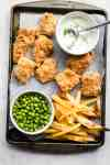 Parchment paper lined baking tray with baked crispy fish and chips on it along with a bowl of peas and homemade tartar sauce