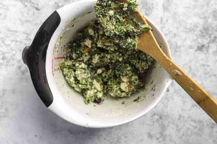 Greek spinach pie with feta mix in a bowl with a wooden spoon