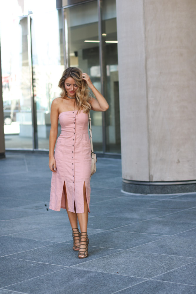 Amber from Every Once in a Style is wearing a pink strapless dress and caged olive heels