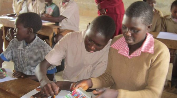 students tracing handprints in Kenya