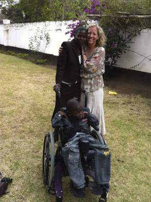 Sara Baker giving a wheelchair to a needy student in Lanet