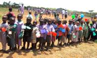 orphaned preschoolers line up for a meal in Kampi Ya Moto