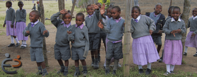 children standing behind a barbed wire fence in Kenya