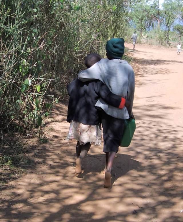 two poor children walking down a dirt road in Kenya