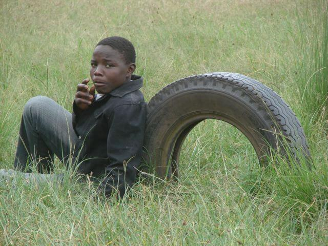 The Promise of an education: Providing scholarships for students like this one sitting against a tire