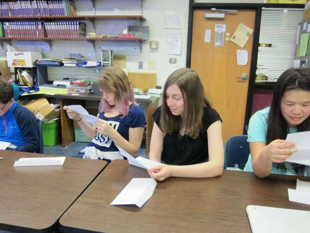 students at Harwood reading a handwritten letter from Kenya