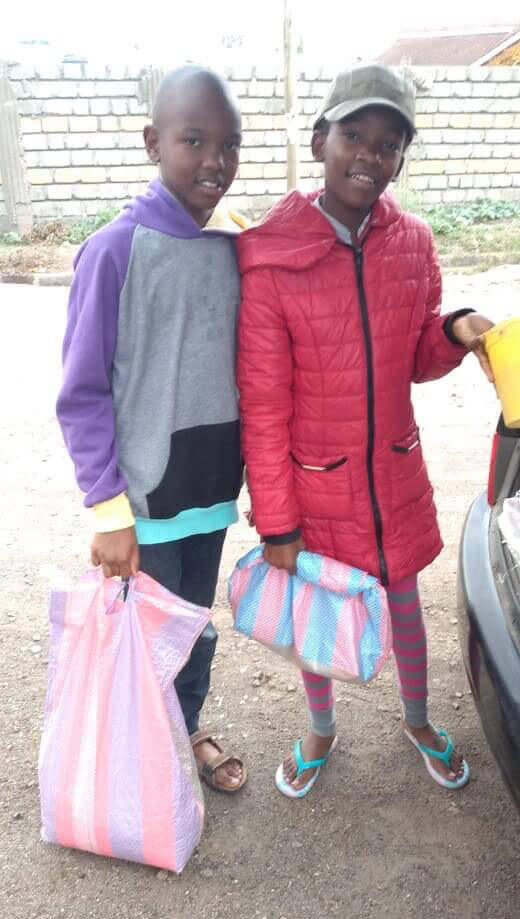 two young girls holding bags of food they received during the coronavirus lockdown