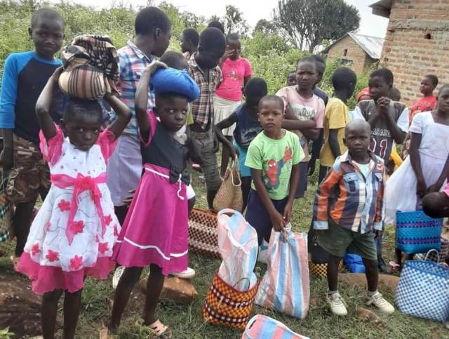 Children with bags of food on their heads are facing a challenging time in Kenya