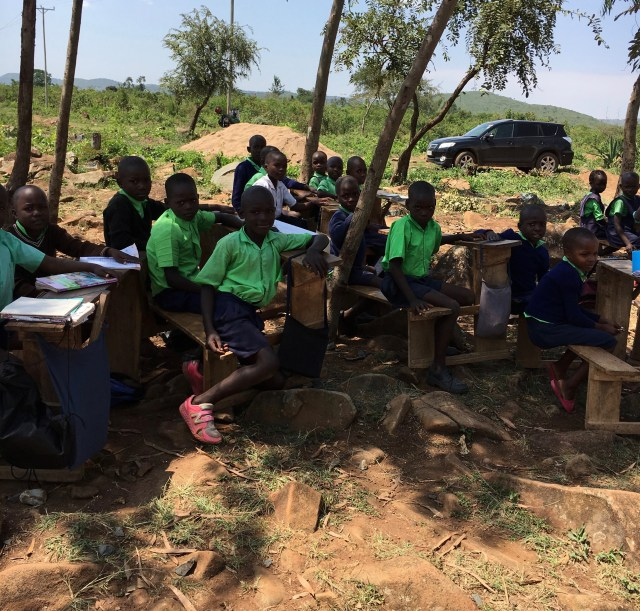 students in Kenya sitting at rough hewn desks under a tree. There is no fence, so securing the perimeter is needed here.