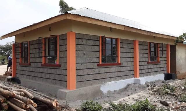 a cinder block building with orange posts at each corner