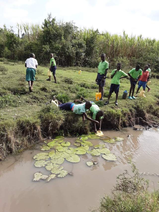 Students collecting muddy water from a river