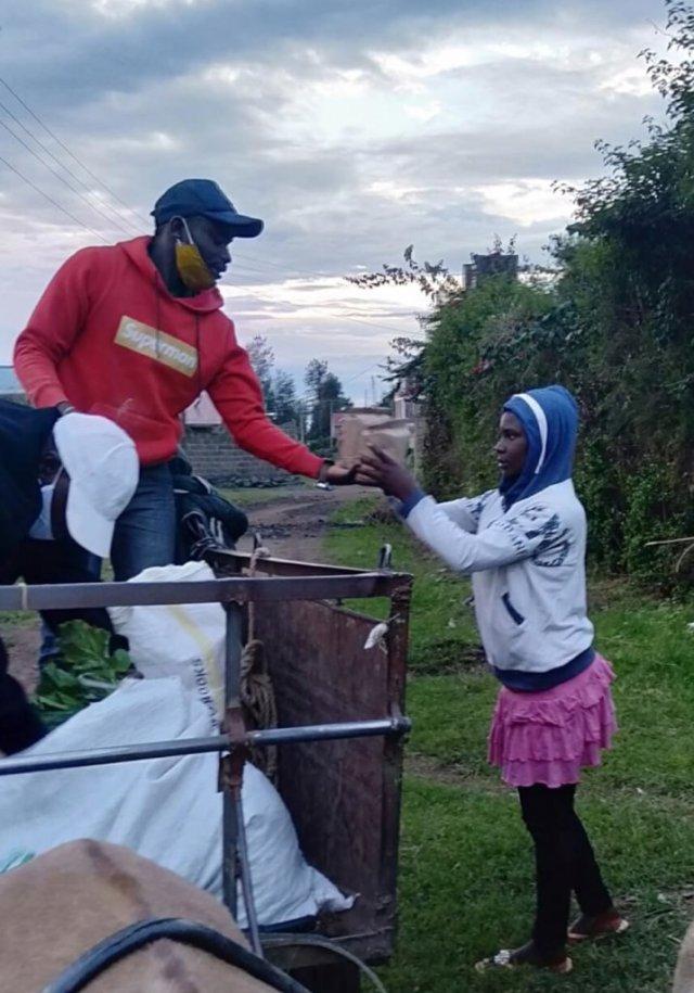 Simon on a cart handing food to a young girl