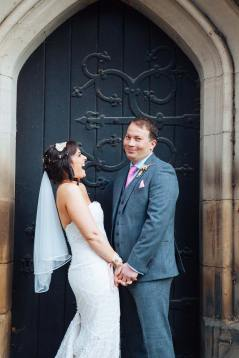 Bride and groom laughing outside the church gate
