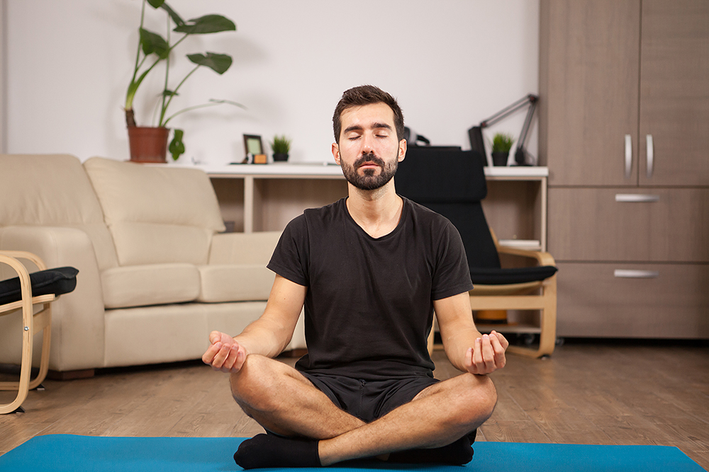 Fit man doing Bound angle yoga pose while he's home in the living room