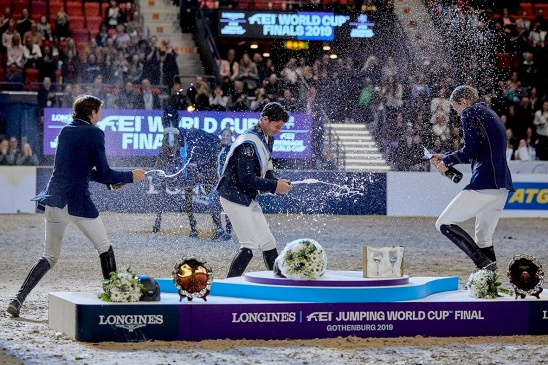Newly-crowned champion, Switzerland's Steve Guerdat (centre) celebrates in style with his compatriot and runner-up Martin Fuchs (left) and third-placed Peder Fredricson from Sweden (right) at the Longines FEI Jumping World Cup™ Final 2019 at the Scandinavium Arena in Gothenburg (SWE) today. (FEI/Liz Gregg)