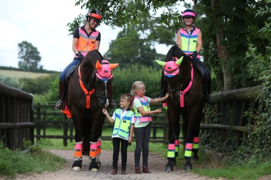 Equisafety - CD Multi-Colour Collection. Group of two women and young children and horses wearing Equisafety items