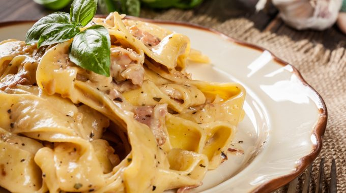 Pappardelle pasta with prosciutto and cheese sauce on a plate. Food and drink