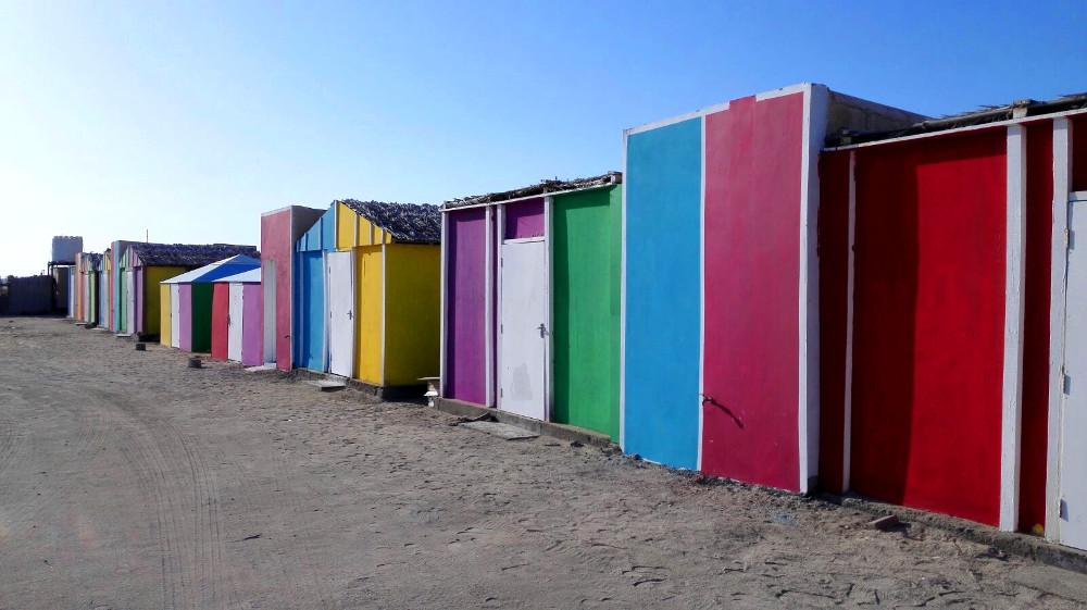 Bunte Holzhütten im Masirah Beach Camp im Oman