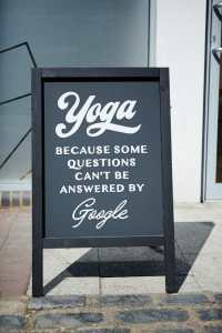 A sandwich board on the street, saying 'yoga, because some questions can't be answered by Google'.
