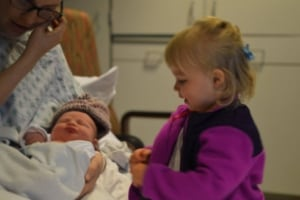 little girl meeting new baby