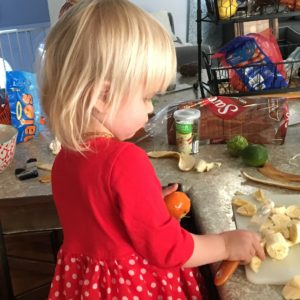 little girl cutting bananas with a plastic knife