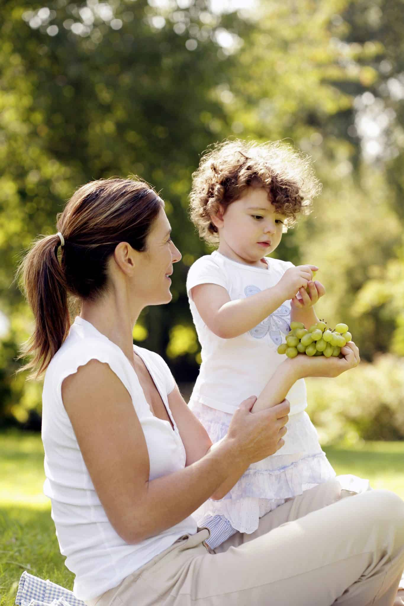 girl getting grape from mother