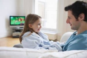 Father and daughter watching TV together and discussing the show
