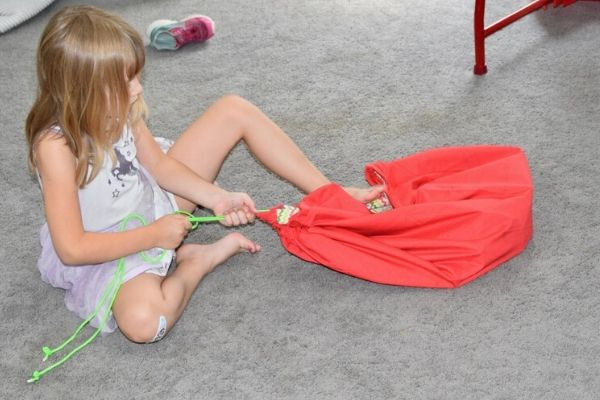 young-girl-closing-Lego-bag