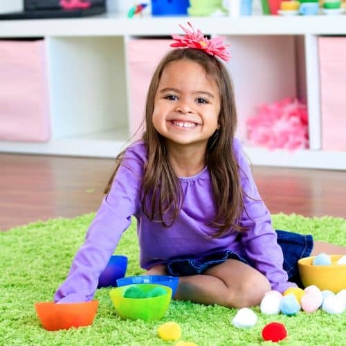 little girl playing with pom poms