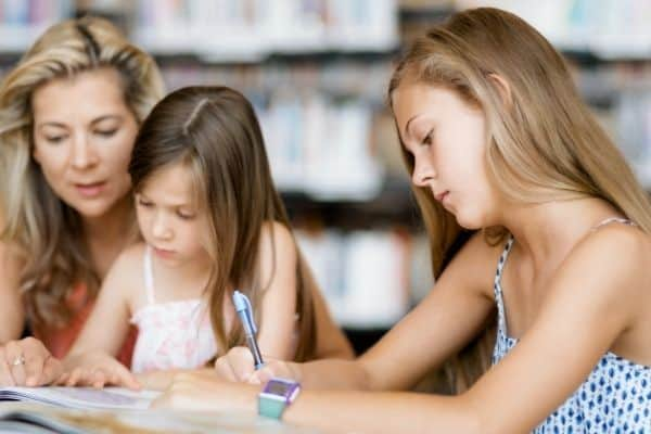 One homeschool child working while mom explains concept to other child