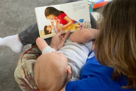 mother Reading diaper changing book to baby