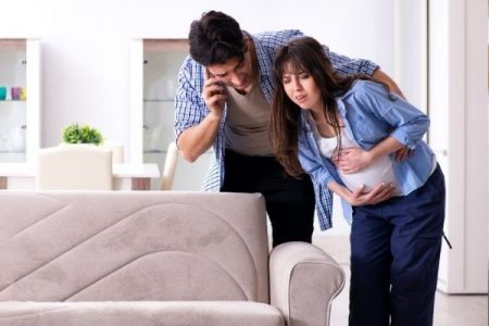 husband on phone while pregnant wife has contractions