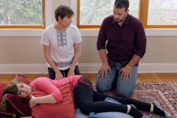 Screen shot from Mama Natural Birth course, where father is kneeling beside midwife and laboring wife who is propped and supported by pillows while resting on her side