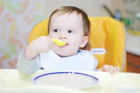 baby eating rice cereal with spoon