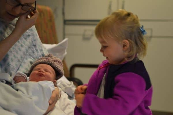Big sister toddler meeting her newborn baby sister