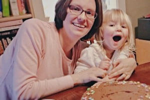 Mother and little girl in front of chocolate cake for weaning party