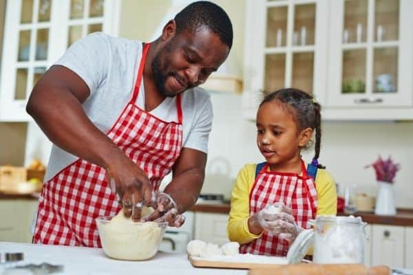 Little girl and daddy wearing matching gingham aprons and kneading dough